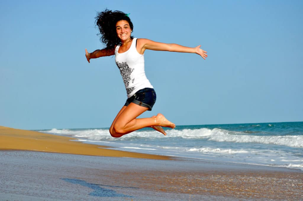 woman smiling and jumping on beach