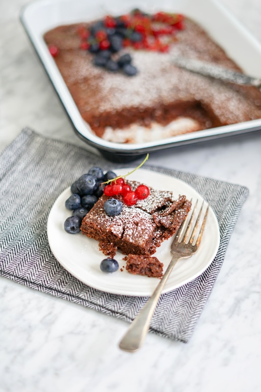 close-up view of a brownie in a small white plate with fresh blueberries and red currants