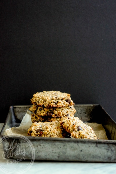 horizontal front view of a pile of cookies in an antique cookie pan with a black background