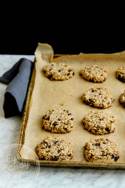 Several cookies on a cookie sheet with unbleached parchment paper on top of a marbled table and black background