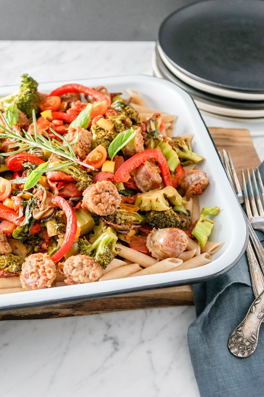 close-up view of a pan with pasta, vegetables and sausage on a wooden board with utensils on the right side