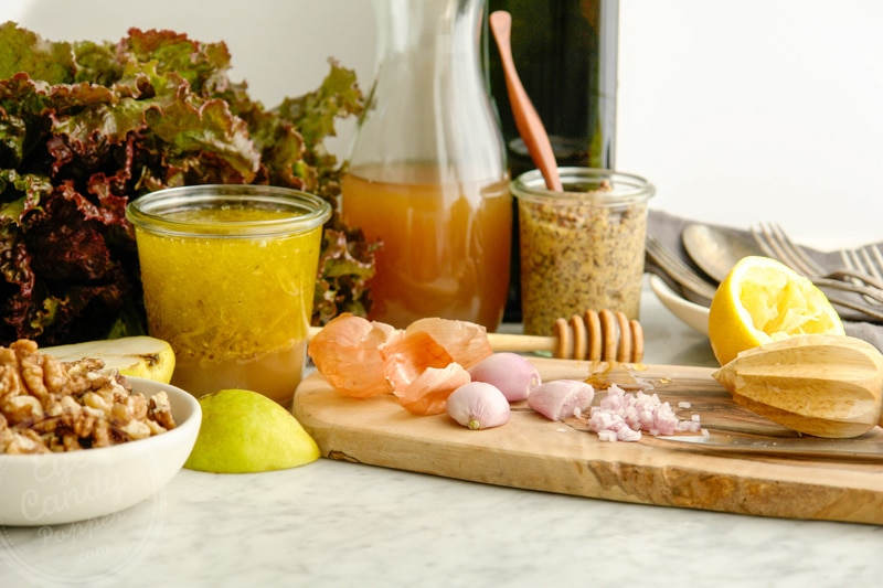 French shallot peeled and cut on a wood cutting board, surrounded by apple cider vinegar, a bottle of olive oil in the background, fresh cut lemon, grainy mustard, walnuts and a red leaf lettuce
