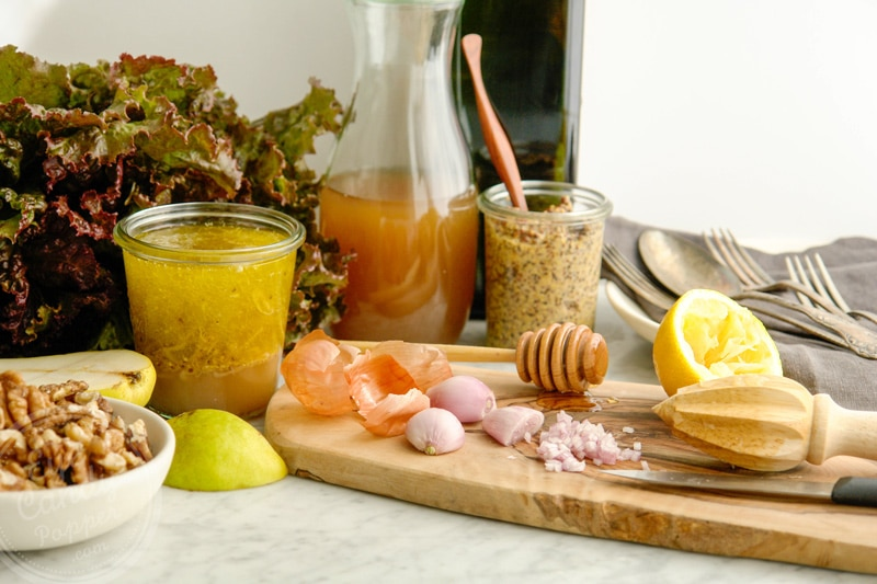 French shallot peeled and cut on a wood cutting board, surrounded by apple cider vinegar, a bottle of olive oil in the background, fresh cut lemon, grainy mustard, walnuts, red leaf lettuce, a pear and some antique forks and spoons in the back on top of a grey napkin