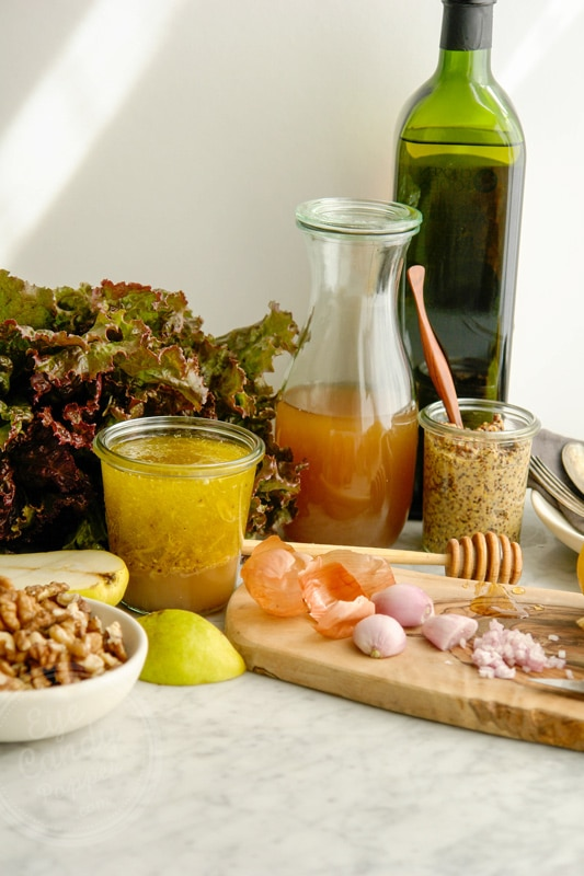 portrait front view. French shallot peeled and cut on a wood cutting board, surrounded by apple cider vinegar, a bottle of olive oil in the background, fresh cut lemon, grainy mustard, walnuts and a red leaf lettuce