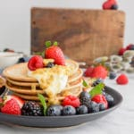black plate with a stack of small pancakes, fresh berries on the side, and a dollop of yogurt and passion fruit dripping on the side of the pancakes