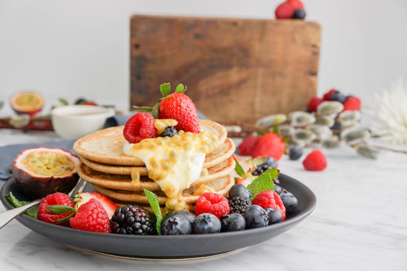 stack of mini pancakes, fresh berries and a dollop of yogurt and passion fruit dripping on the side