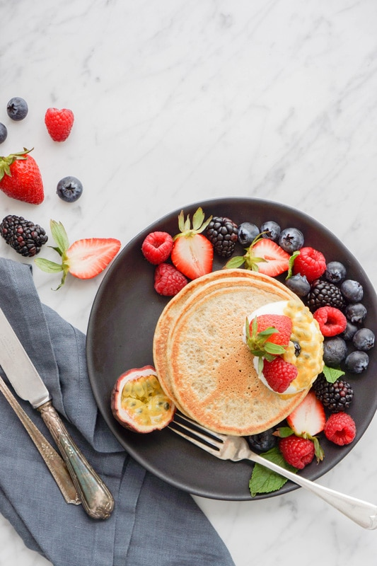 aerial view of a stack of small pancakes on a black plate, fresh berries on the side