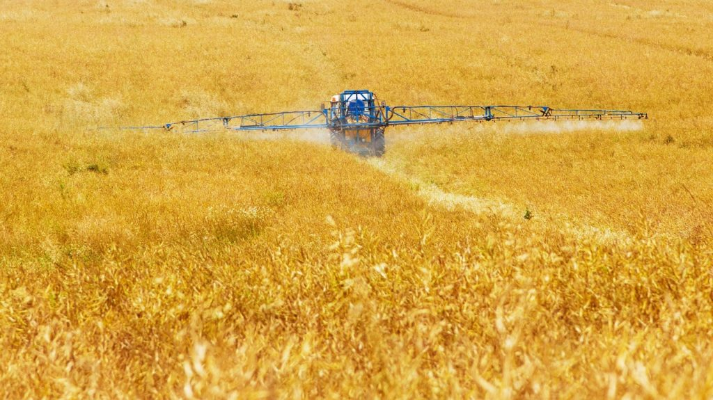 A field with pesticides being sprayed