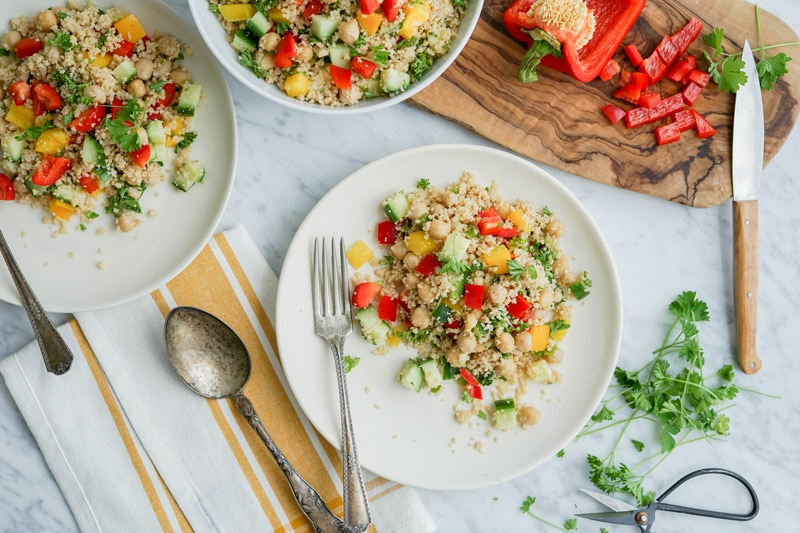 Top horizontal view of 3 white plates with couscous salad with cut red pepper on a wood cutting board on top of a white marble table