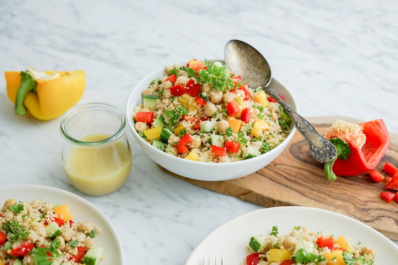 45 degree angle view of a close-up white bowl filled with couscous salad and vegetables with dressing in a small bottle on the left
