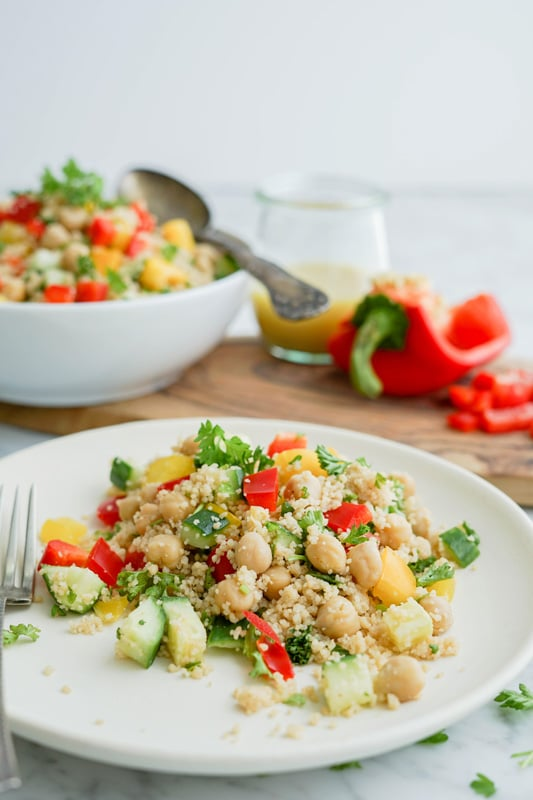 Front vertical close-up of a white plate with couscous salad in it with red and yellow pepper, cucumber, chickpeas and parsley