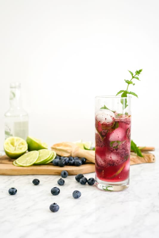front close-up of a tall glass with a blueberry drink with fresh blueberries and limes on the left
