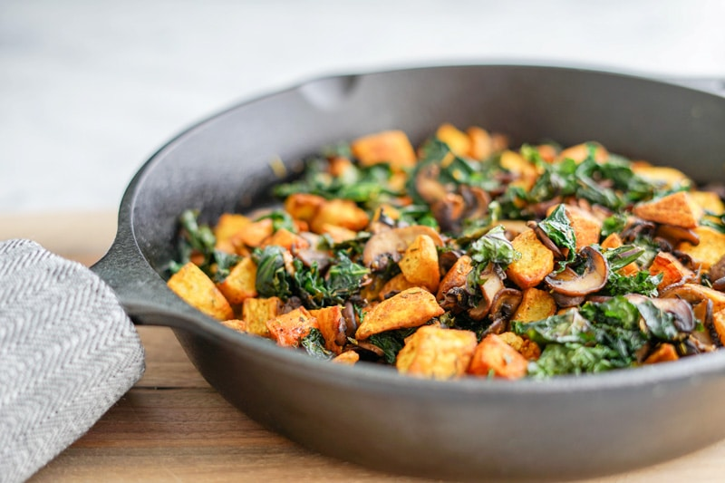 front horizontal view of a Potato, Mushroom and Kale Hash in a cast-iron skillet
