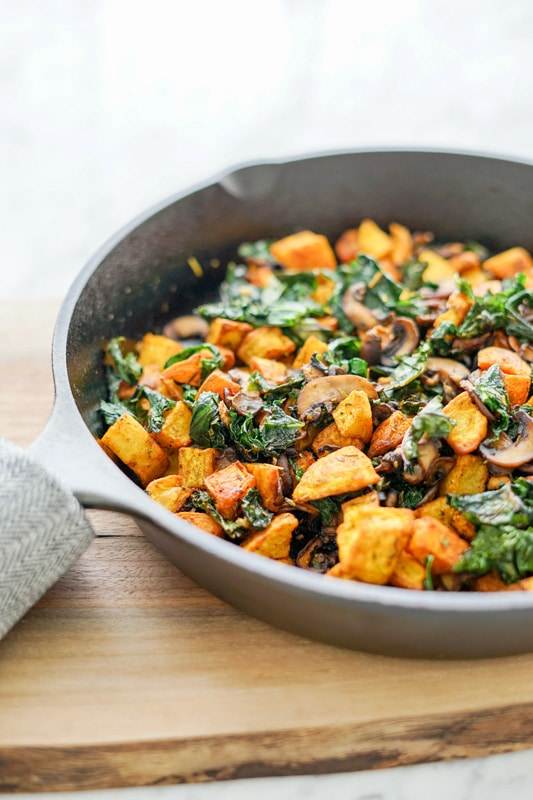 front vertical view of a Potato, Mushroom and Kale Hash in a cast-iron skillet