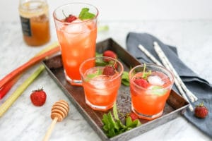 eye-level view of 3 glasses of strawberry rhubarb lemonade on a metal tray with fresh strawberries