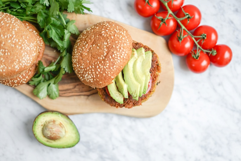 top down view of sweet potato chickpea burger with avocado slices on top and fresh cilantro on the side
