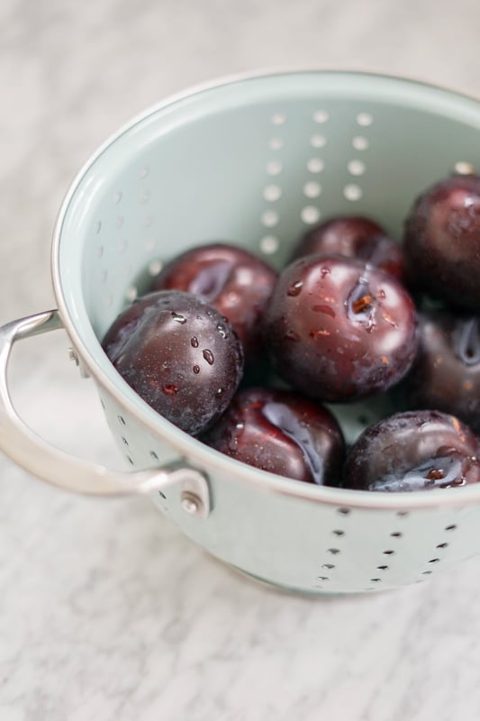 eye-level view of several purple plums in a light blue colander