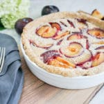 close-up view of a plum tart in a white dish with 2 vintage forks on a linen napkin on the side
