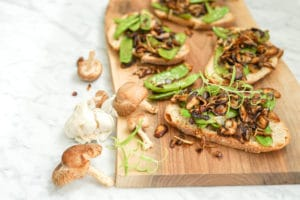 horizontal view of Roasted Mushroom, Onion and Snow Pea Crostini on top of a wood board with fresh mushrooms on the side