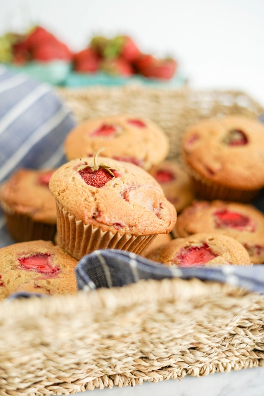 Close-up of Strawberry Maple Muffins in a straw basket and a blue striped linen