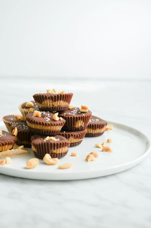 Front view of peanut butter cups piled on a white plate on a white marble table