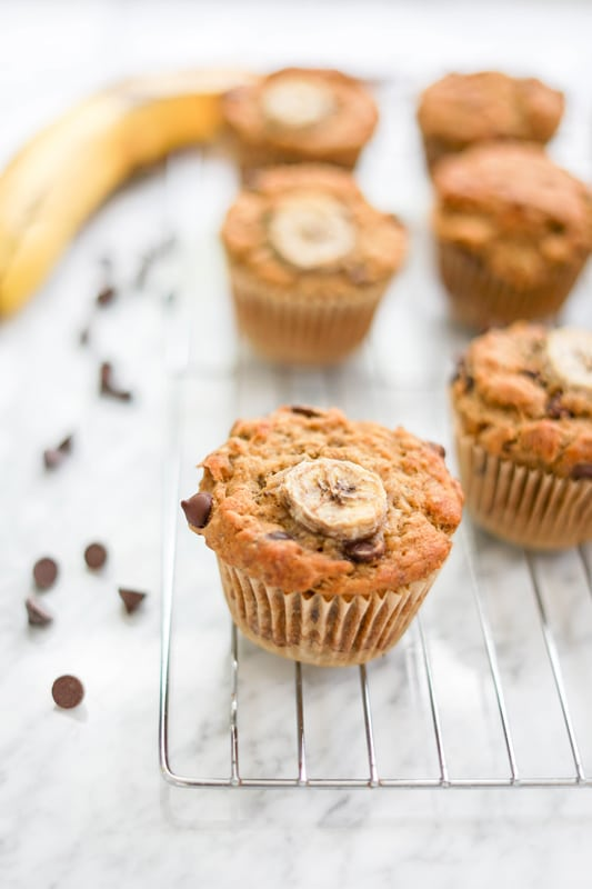 close-up front view of vegan banana chocolate chip muffin on a cooling rack on a white marble