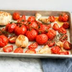 front view of baking sheet filled with cooked tomatoes and garlic