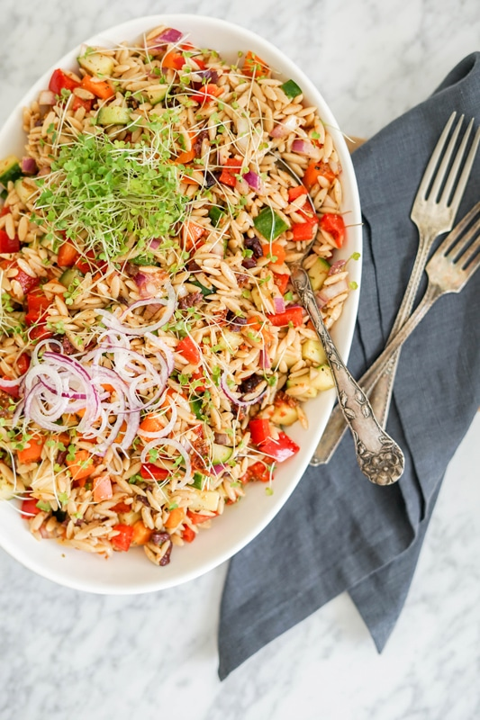 aerial view of a large platter with orzo pasta salad in it and vintage forks on a dark blue napkin on the side