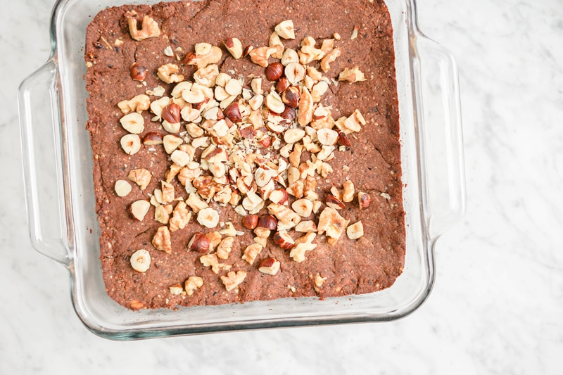 Black bean brownies in a square glass pan with chopped nuts on top