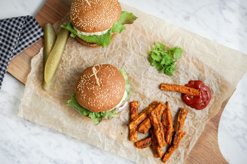 aerial view of 2 Black Bean Burgers with Sweet Potato Wedges and pickles on the side