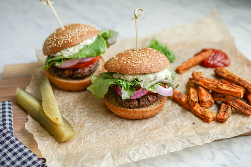 front view of 2 Black Bean Burgers with Sweet Potato Wedges and pickles on the side