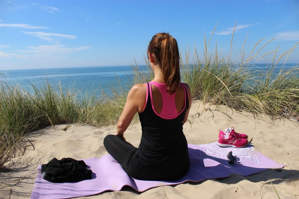 A woman in a yoga meditation pose on the beach