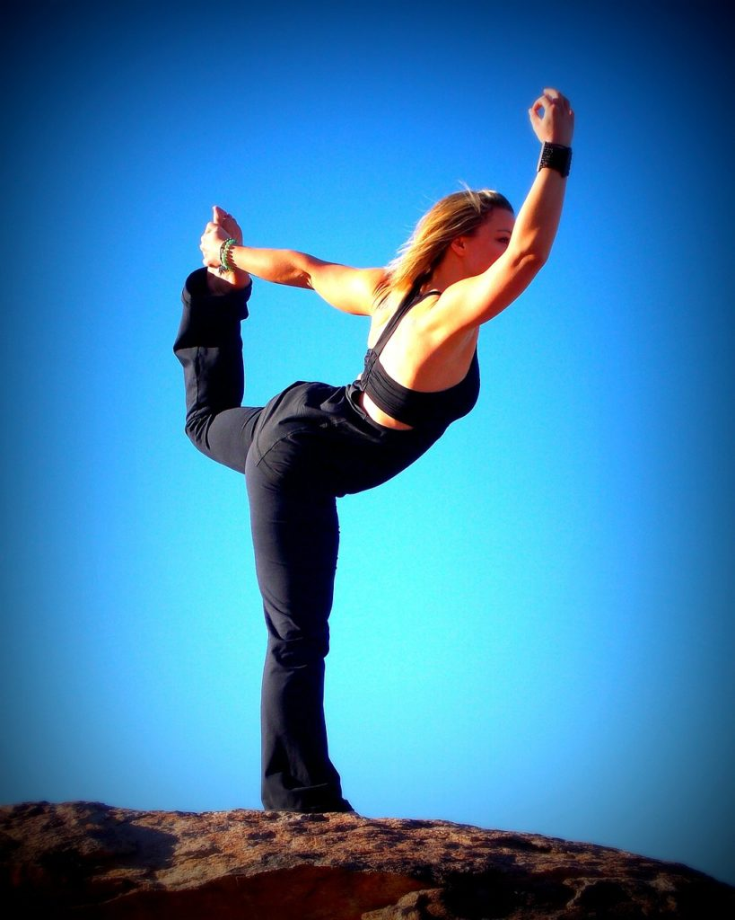 A woman standing on some rocks on one leg in a yoga pose