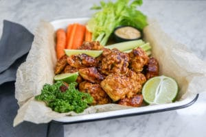 Close-up of cauliflower carrot wings and cut celery and carrot with cashew dip in background