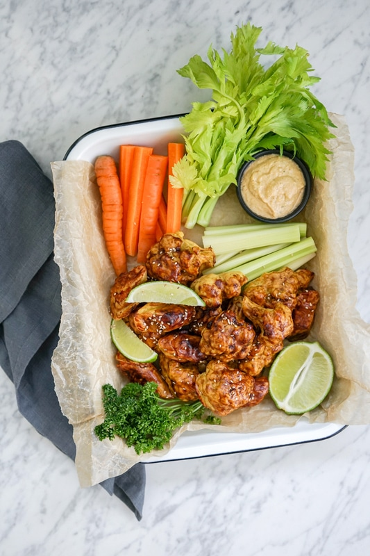aerial view of a platter with cauliflower wings and crudités on a white marble table