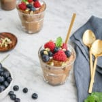 Close-up of a glass filled with chocolate avocado mousse and fresh berries on top, with a bowl of blueberries on the left and 2 golden spoons on a blue napkin on the right