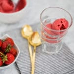eye-level view of strawberry sorbet in glass with 2 golden spoons and fresh strawberries on the left side