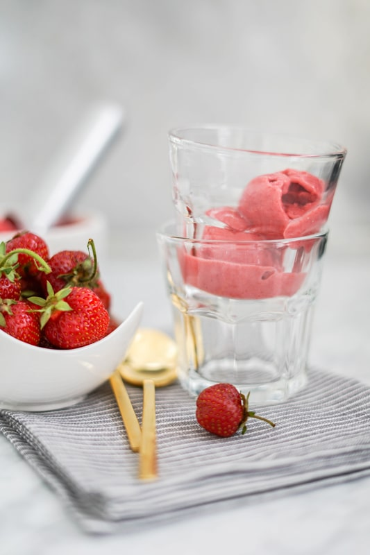 Strawberry sorbet in a glass with fresh strawberries on the side