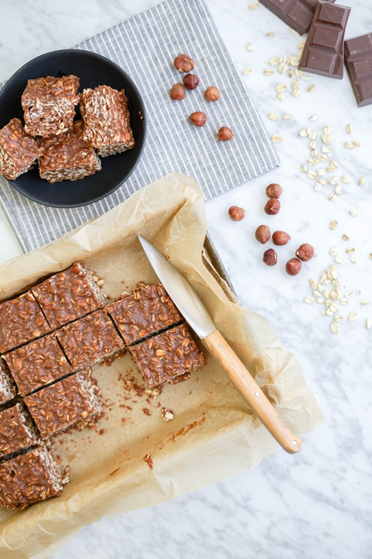 top vertical view of a tray of chocolate fudge oatmeal bars on a white marble table and scattered hazelnuts and oat flakes on the right side