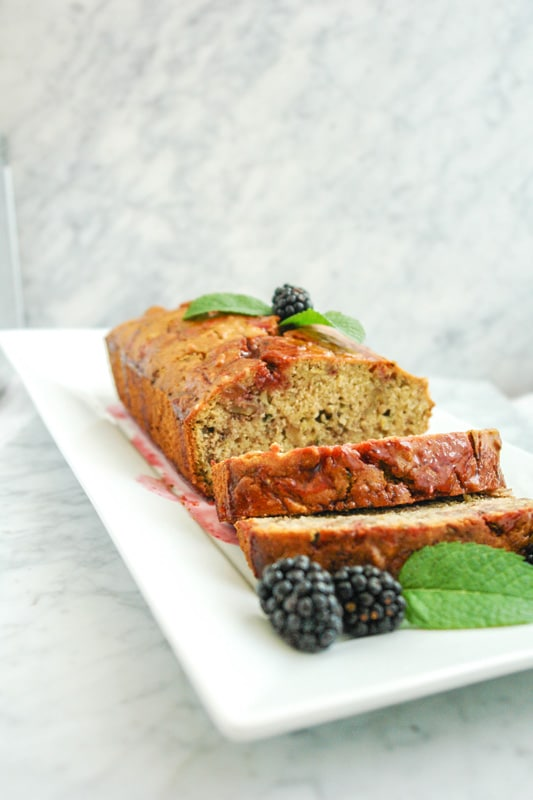a Lemon Zucchini Bread with blackberries and mint leaves on a rectangular white plate on top of white marble