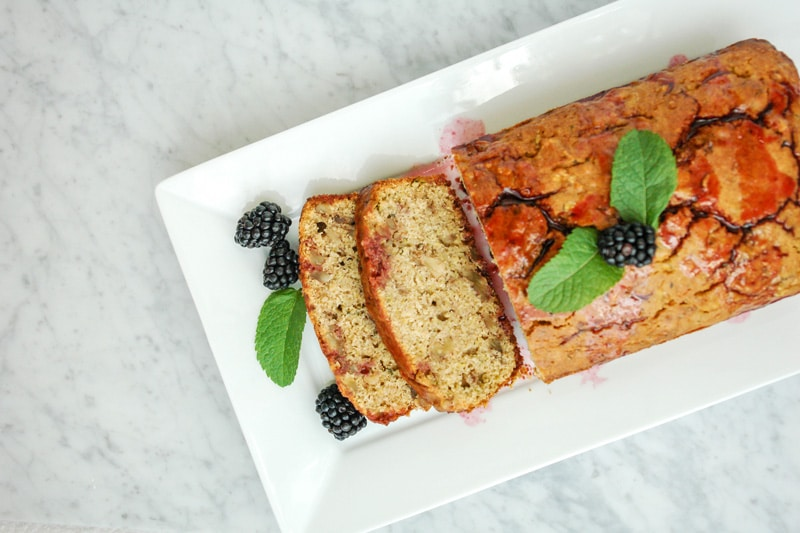 aerial view of a Lemon Zucchini Bread with blackberries and mint leaves on a rectangular white plate on top of white marble