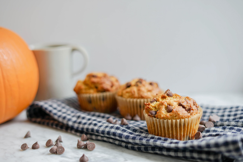horizontal front view of 3 pumpkin chocolate chip muffins on a checkered napkin