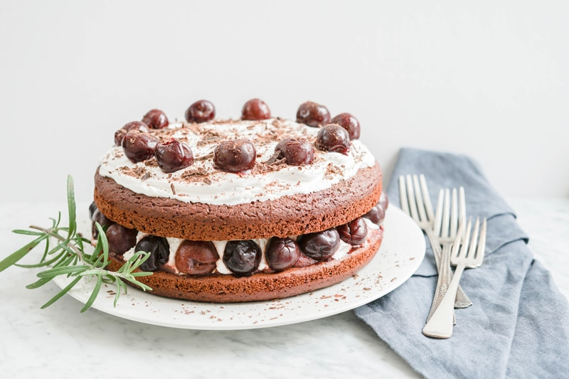 A healthy chocolate cake with cherries and coconut whipped cream