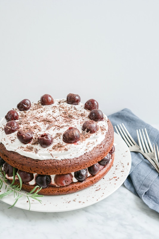 Chocolate cake with coconut whipped cream and cherries on a white plate