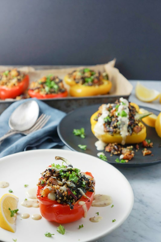 quinoa and roasted vegetable-stuffed yellow and red peppers in a black and white plates with more stuffed peppers in background