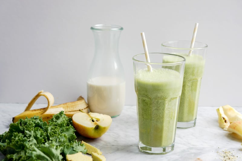 front view of 2 green smoothies, fresh kale, apple and banana on the left and a glass container of nut milk in the back