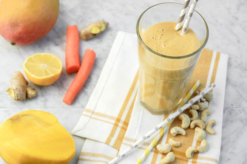 a big glass of Smoothie with stripped paper straws. Mango, carrots, lemon, and ginger on the left and cashews on the right side