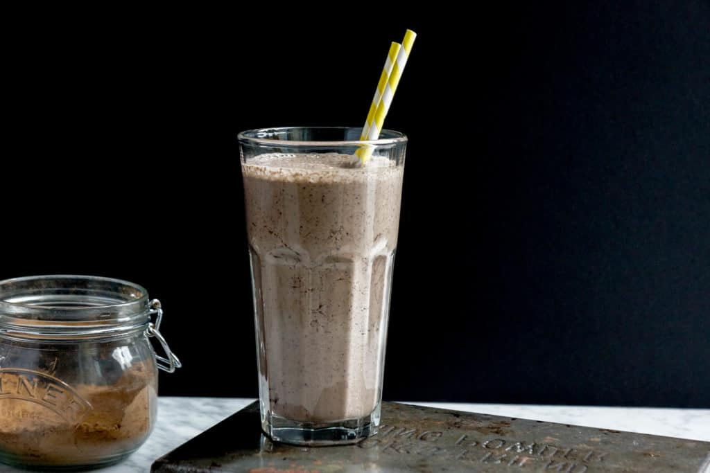a big glass of chocolate smoothie with 2 yellow stripped straws in it on a black background, with a jar of cocoa powder on the left side