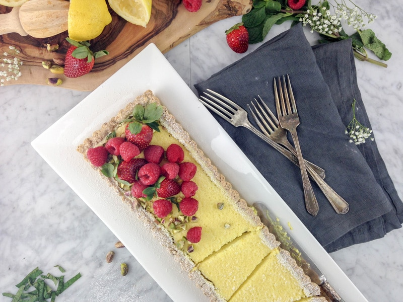 aerial view of a rectangular lemon tart on a white plate, with raspberries and strawberries on top, 3 antique forks on a grey napkin on the right side. Everything is set on top of a white marble table top