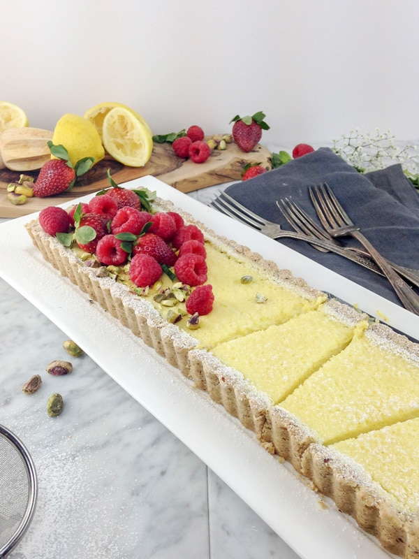 front view of a rectangular lemon tart cut in pieces on a white plate, with raspberries and strawberries on top, and some squeezed lemon halves and fresh berries on a wood board in the background. antique forks on a grey napkin on the right side